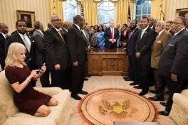 Counselor to the President Kellyanne Conway (L) checks her phone after taking a photo as US President Donald Trump and leaders of historically black universities and colleges pose for a group photo in the Oval Office of the White House before a meeting with US Vice President Mike Pence February 27, 2017 in Washington, DC. / AFP / Brendan Smialowski (Photo credit should read BRENDAN SMIALOWSKI/AFP/Getty Images)
